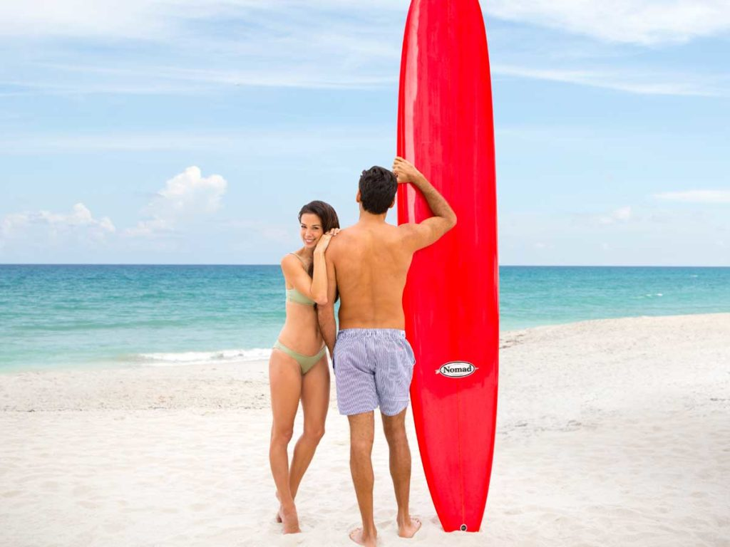 Couple with surfboard at Sunny Isles Beach