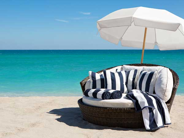 Big lounge chair and umbrella on the beach.