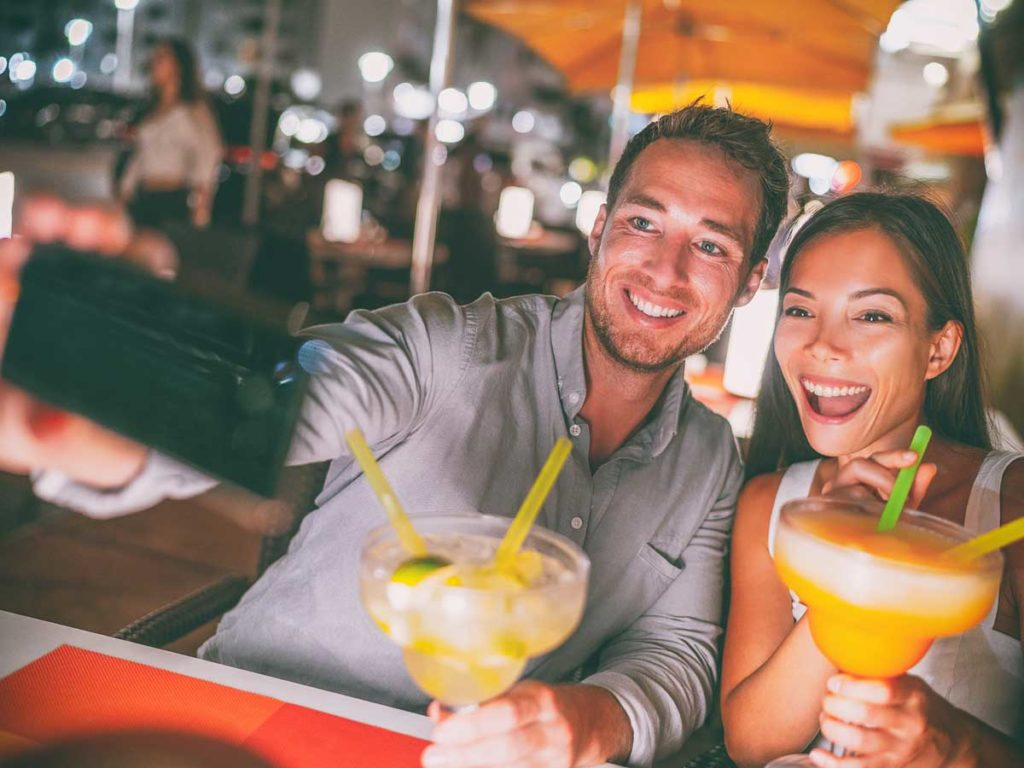 couple having cocktail taking selfy
